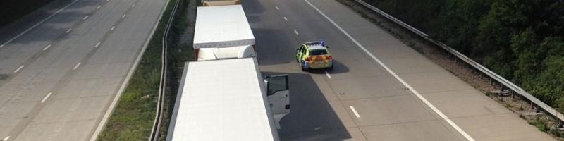 A police car drives the wrong way along the closed M20 during Operation Stack. Click to enlarge